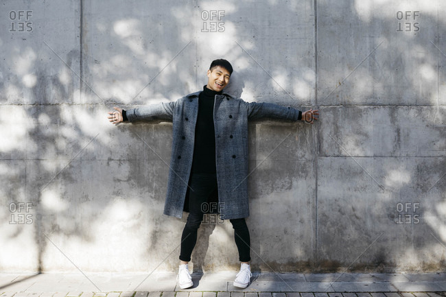 Laughing young man wearing turtleneck pullover and grey coat standing in front of concrete wall