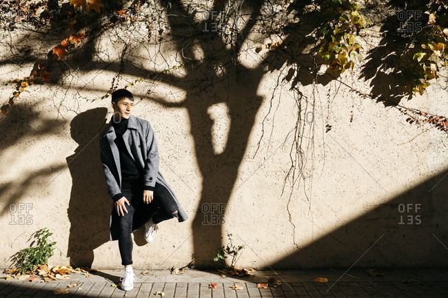 Relaxed young man leaning against wall in autumn