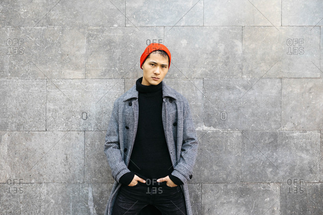 Portrait of stylish young man wearing cap- black turtleneck pullover and grey coat