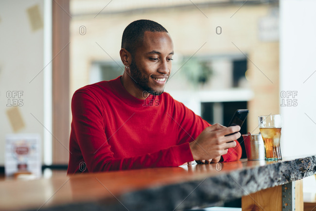Smiling young man wearing red pullover at counter of a bar with soft drink and mobile phone