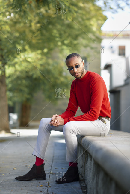 Portrait of fshionable young man wearing red pullover and sunglasses sitting on stone bench