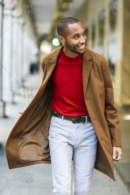 Fashionable young man wearing red pullover and brown coat walking along arcade