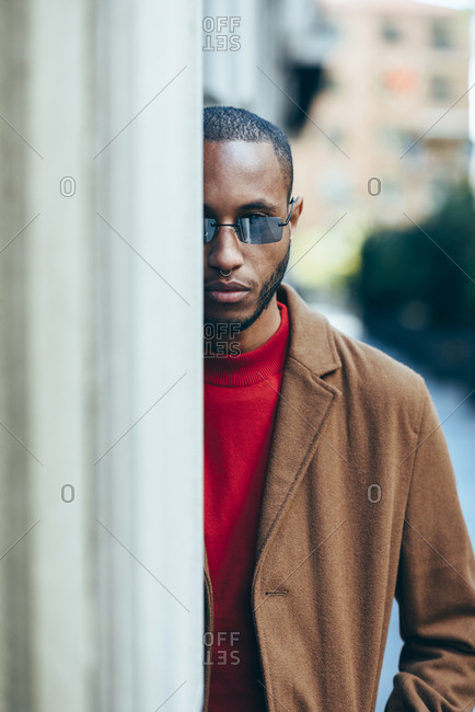 Portrait of bearded young man with nose piercing and sunglasses hiding behind wall