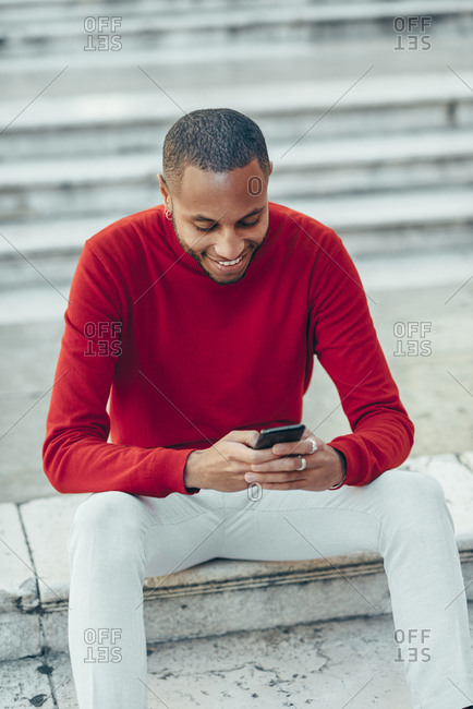 Smilig young man wearing red pullover sitting on stairs using cell phone