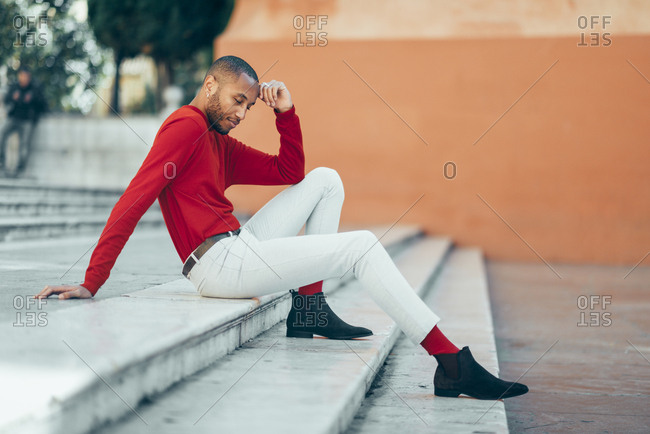 Fashionable young man wearing red pullover and socks sitting on stairs relaxing