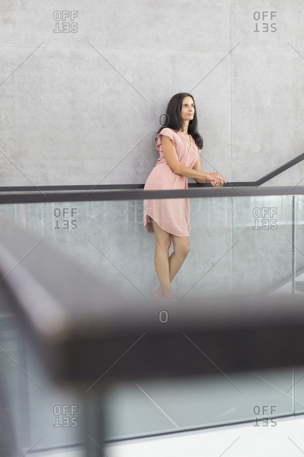 Mature woman wearing pink summer dress leaning on railing