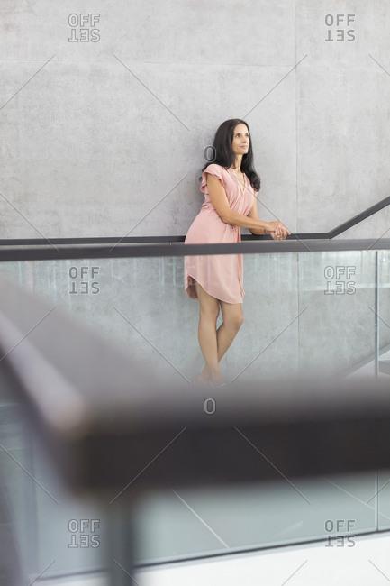 Mature woman wearing pink summer dress leaning on railing