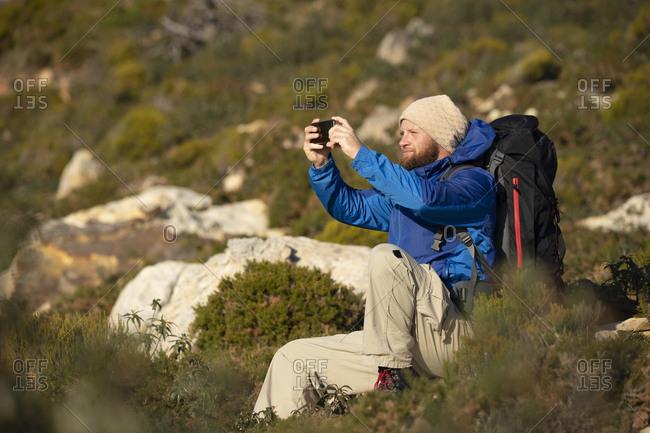Spain- Andalusia- Tarifa- man on a hiking trip sitting down taking a selfie