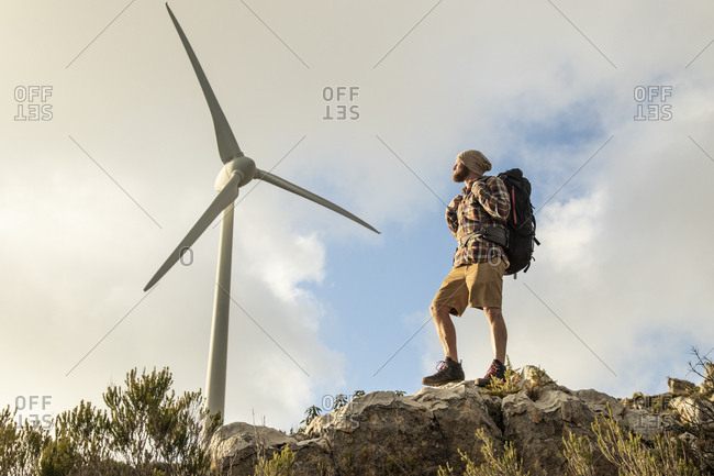 Spain- Andalusia- Tarifa- man on a hiking trip standing on rock with wind turbine in background