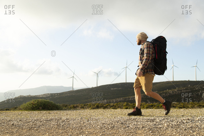 Spain- Andalusia- Tarifa- man on a hiking trip walking on dirt road with wind turbines in background