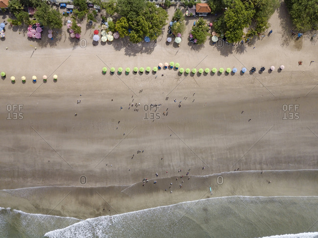 Bali- Kuta Beach- row of beach umbrellas and people on the beach- aerial view