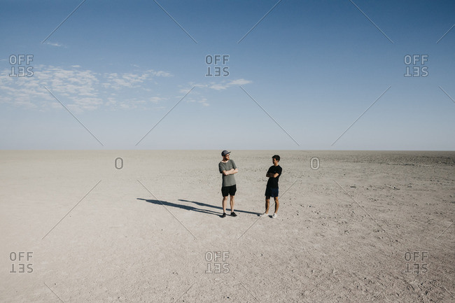 Two young man standing in the desert- with arms crossed