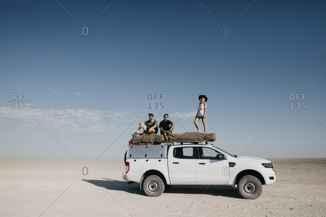 Friends on a safari- standing on their off-road vehicle
