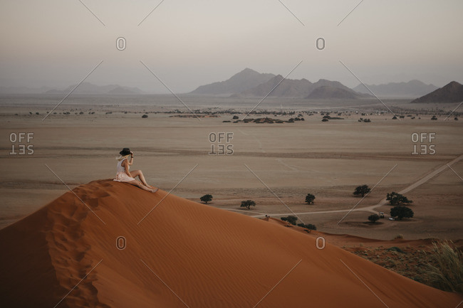 Namibia- Namib desert- Namib-Naukluft National Park- Sossusvlei- woman sitting on Elim Dune at sunset