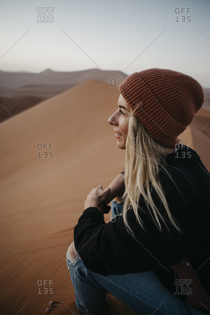 Namibia- Namib desert- Namib-Naukluft National Park- Sossusvlei- smiling woman sitting on Dune 45 at sunrise