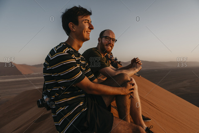 Namibia- Namib desert- Namib-Naukluft National Park- Sossusvlei- two smiling men sitting on Dune 45 at sunrise