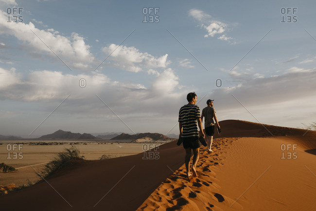 Namibia- Namib desert- Namib-Naukluft National Park- Sossusvlei- two men walking on Elim Dune at sunset