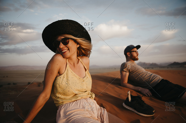 Namibia- Namib desert- Namib-Naukluft National Park- Sossusvlei- happy couple sitting on Elim Dune at sunset