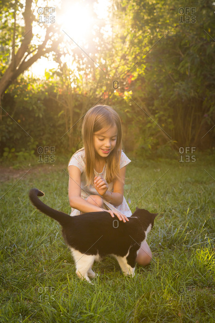 Smiling little girl stroking cat in the garden