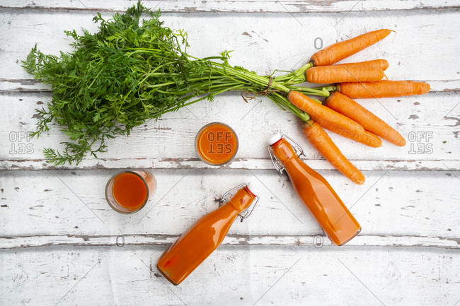 Carrots- glasses of carrot juice and swing top bottles on wood- from above