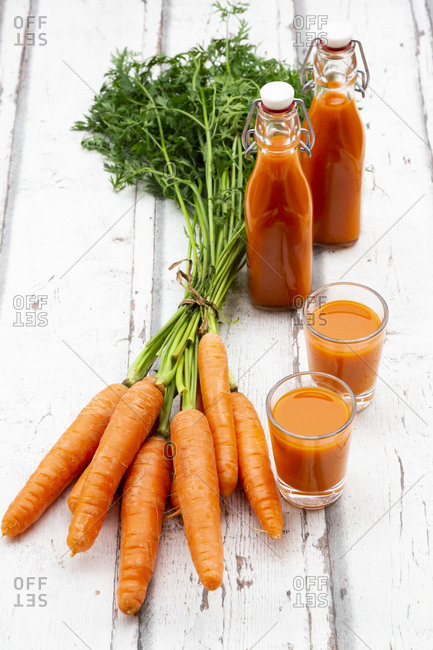 Carrots- glasses of carrot juice and swing top bottles on wood