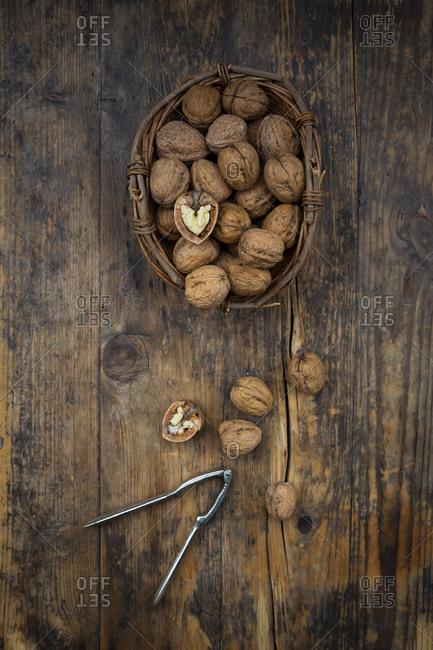 Wickerbasket of walnuts and nutcracker on wood