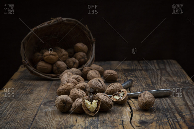 Whole and cracked walnuts- nutcracker and wickerbasket on wood