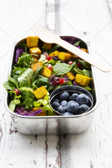 Mixed salad with roasted tofu- red cabbage- pomegranate seeds- blueberries and curcuma in lunch box