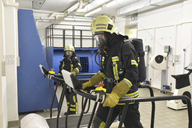 Two firefighters with respirator and air tank exercising in exercise room
