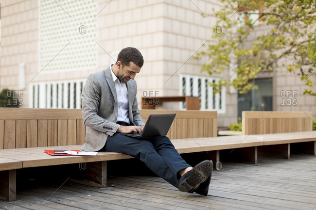 Smiling businessman sitting on a bench using laptop