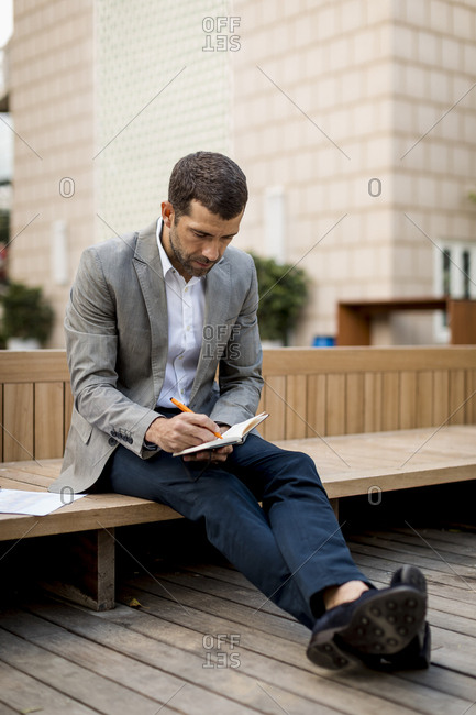 Businessman sitting on a bench writing into diary