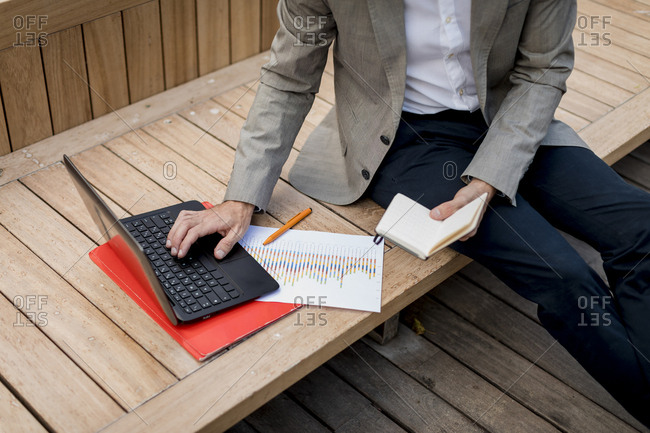Close-up of businessman sitting on a bench using laptop and diary