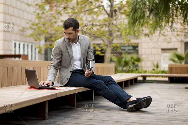 Businessman sitting on a bench using laptop