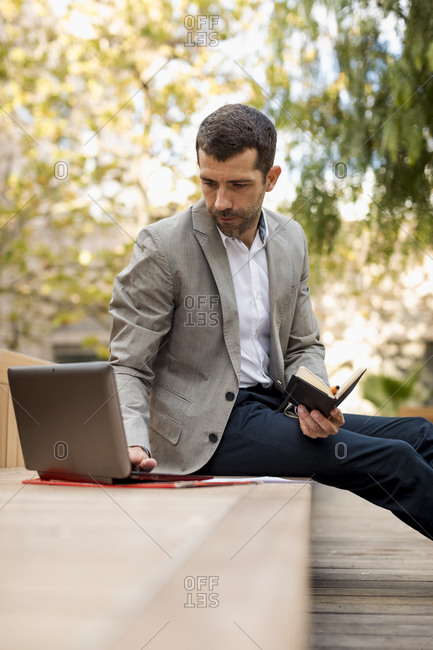 Businessman sitting on a bench using laptop and diary