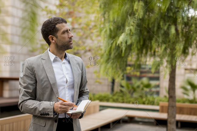 Businessman standing outdoors writing into notebook