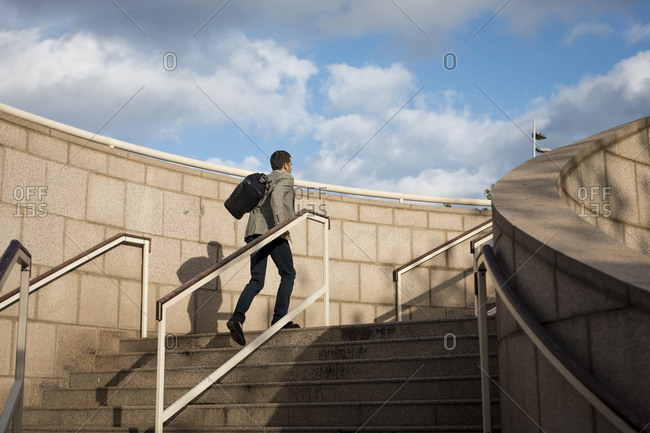 Businessman with bag walking upstairs