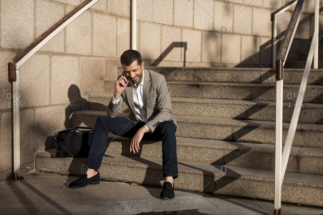 Smiling businessman with bag sitting on stairs talking on cell phone