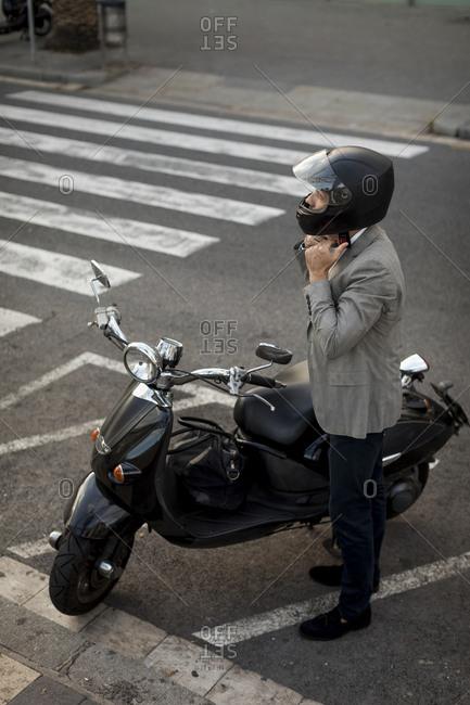 Businessman next to motorscooter putting on helmet