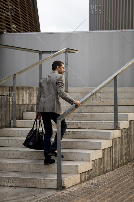 Businessman with bag walking upstairs in the city