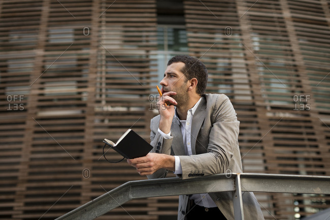 Businessman standing in the city holding a notebook