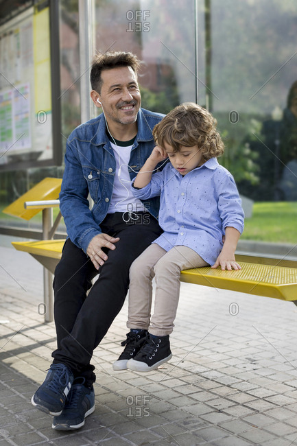 Father and son sitting at tram stop in the city sharing earbuds