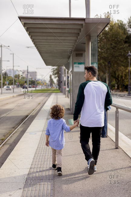 Rear view of father and son walking hand in hand at tram stop in the city