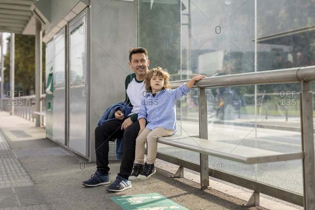 Father and son sitting at tram stop in the city