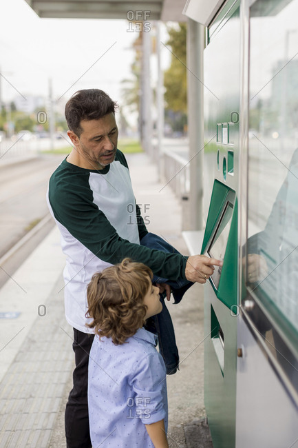 Father and son using ticket machine at tram stop in the city
