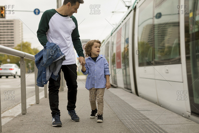 Smiling father and son walking hand in hand at tram stop in the city