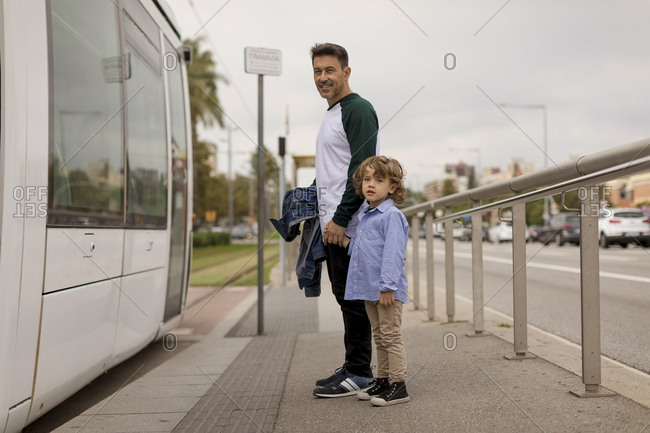 Smiling father and son hand in hand at tram stop in the city