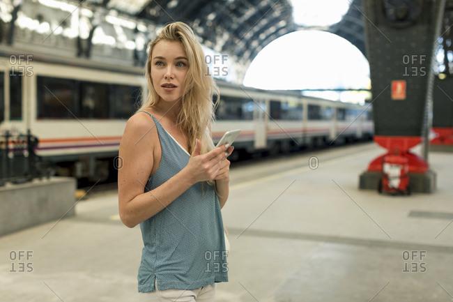 Young woman with cell phone at the train station looking around