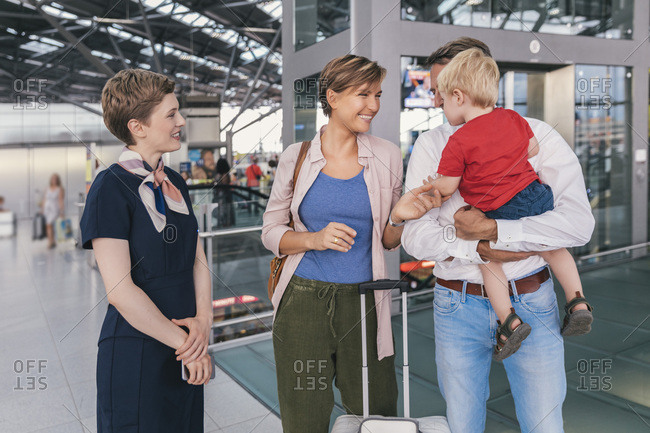 Airline employee talking to family with toddler son at the airport