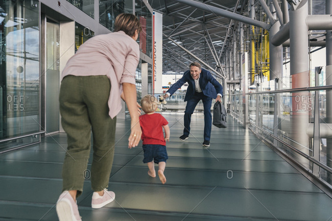 Happy child running into arms of travelling businessman at the airport