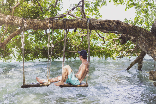 Mexiko- Yucatan- Quintana Roo- lagoon of Bacalar- man sitting on tree swing above the water